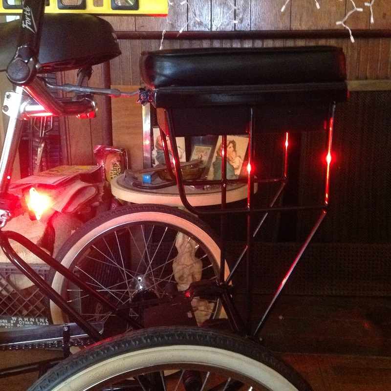 companion bike seat on a tricycle glowing red